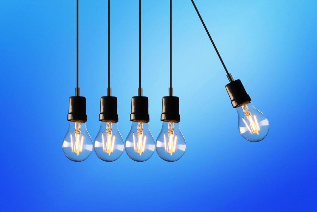 Blue background with 5 dangling light bulbs in wires one is about to hit the others like an office desk toy